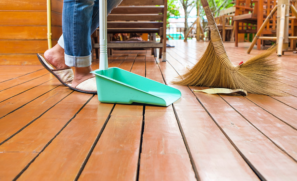 A person sweeping a deck.