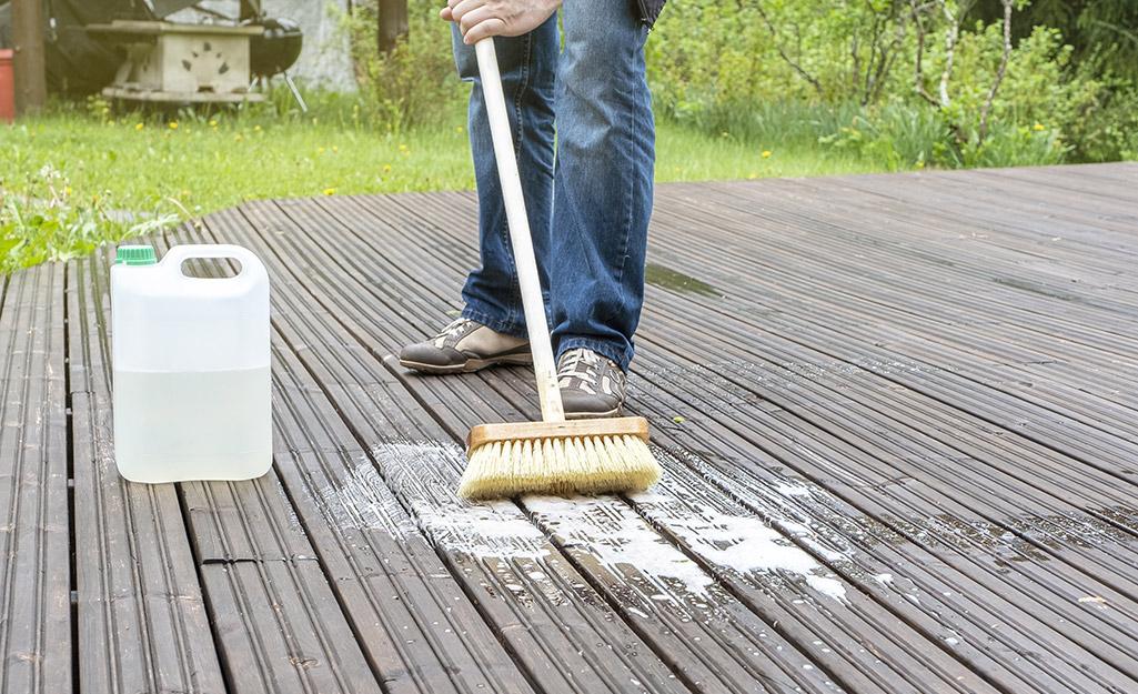 A person scrubbing a deck with a broom.