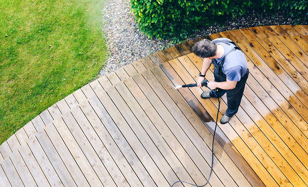 A person pressure washing a deck.