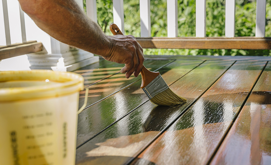A person applying stain to a deck.