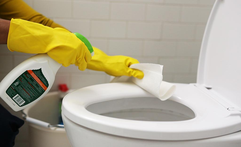 Một người đeo găng tay cao su để làm sạch nhà vệ sinh.