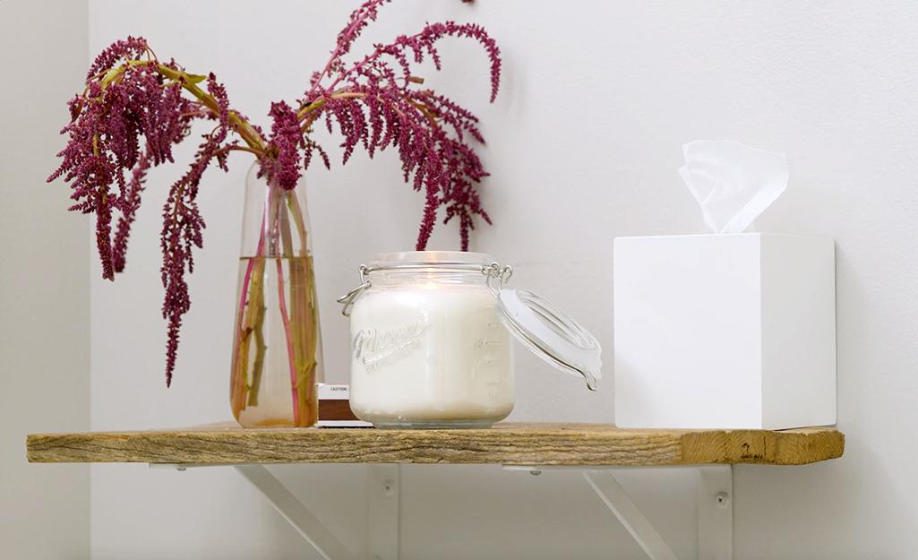 Một ngọn nến, hoa và khăn giấy nằm trên kệ phòng tắm.