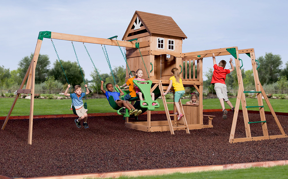 Children play on a swing set that has cushioning material beneath it for safety.