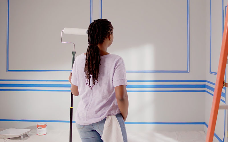 A woman taping off a room in preparation for painting.