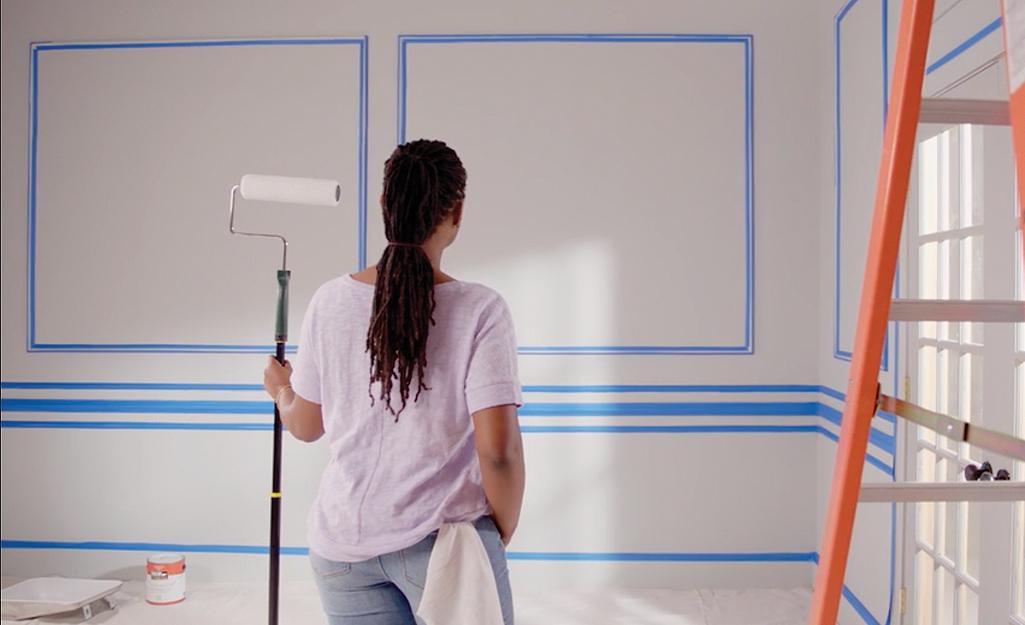 Một người phụ nữ cầm một cây lăn sơn đã sẵn sàng để sơn những bức tường chuẩn bị sẵn của mình.