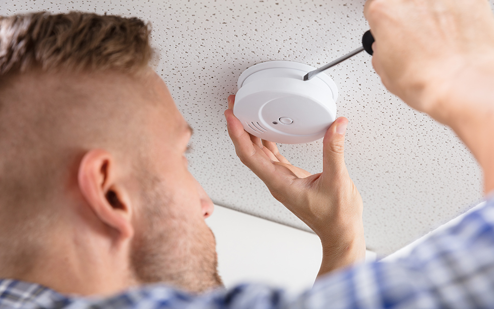 A person mounts a smoke alarm on the ceiling.