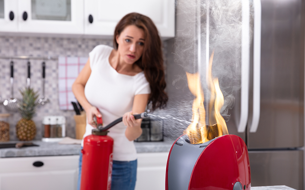 A person uses a fire extinguisher to put out a small kitchen fire.