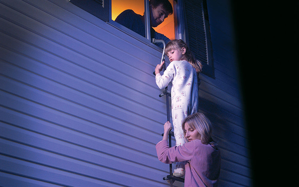 Family members hang onto a second floor fire escape ladder.