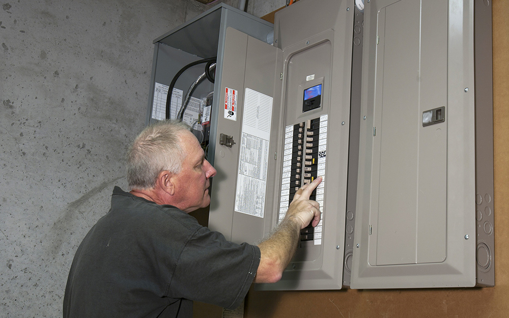 A man shuts off power at a home control panel.