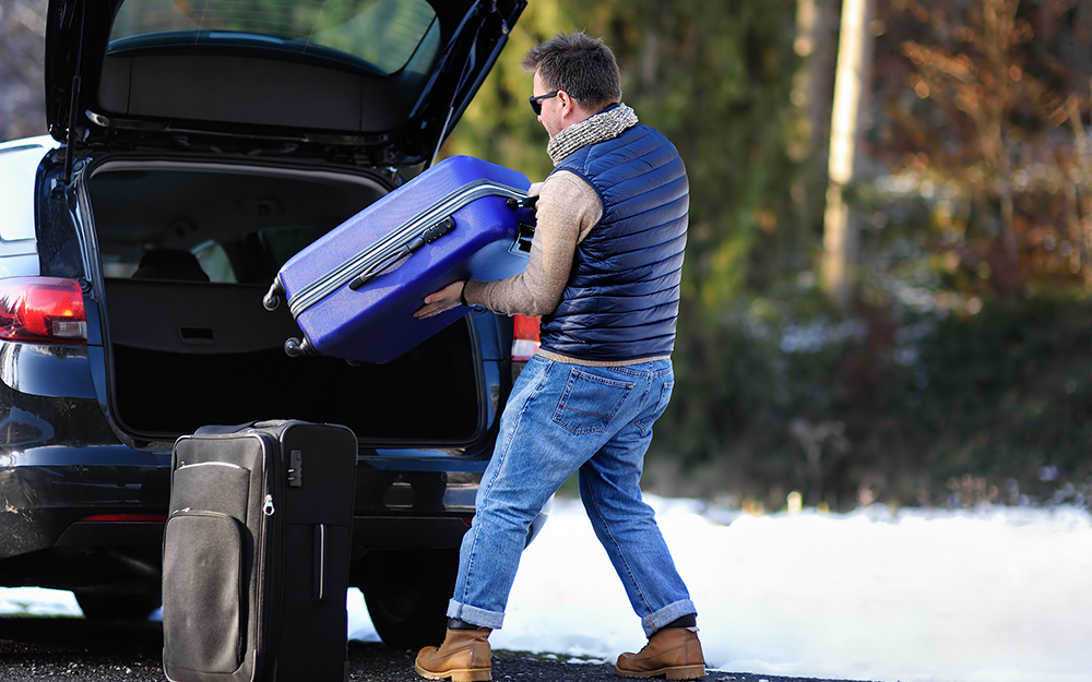 A man packs luggage in the back of his car.