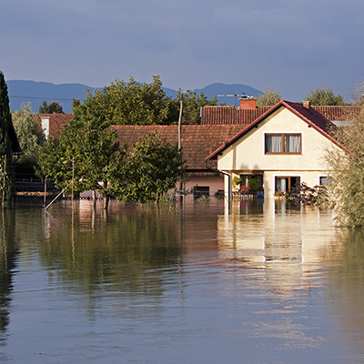Floodwaters rise above the front yard of a house.