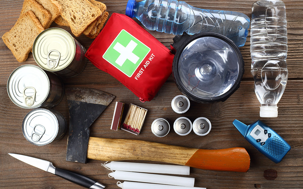 Emergency supplies including a first aid kit and food are arranged on a table.