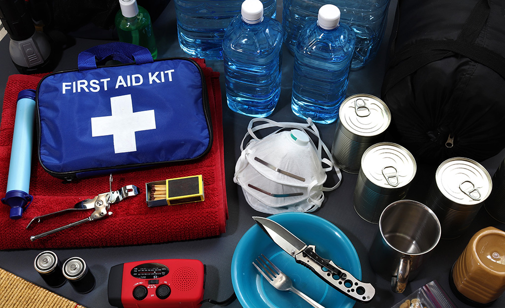 First aid kit, water and other emergency supplies sitting on a table.