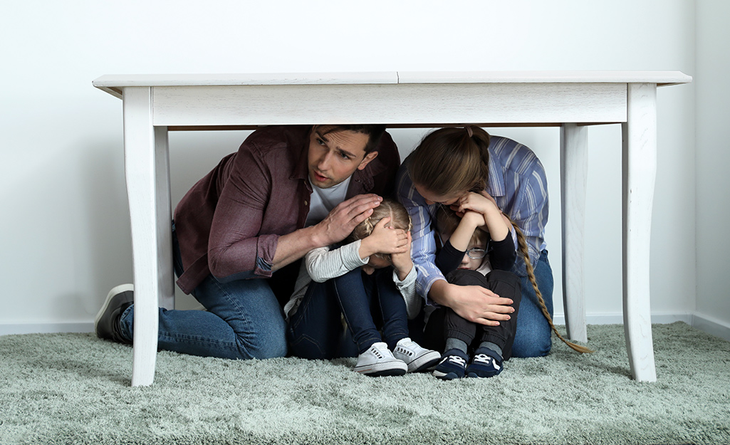 A family takes cover under a table.