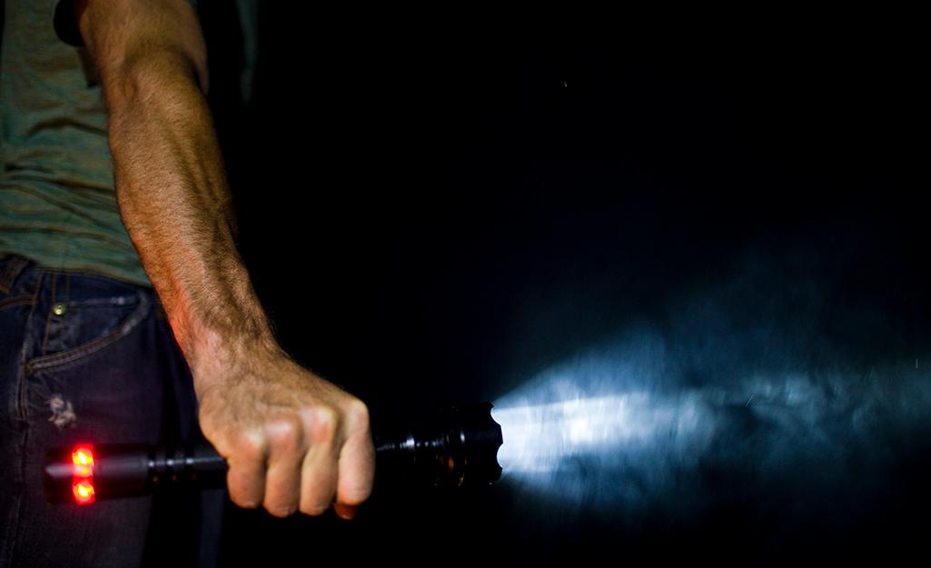 A man holding a flashlight in the dark.