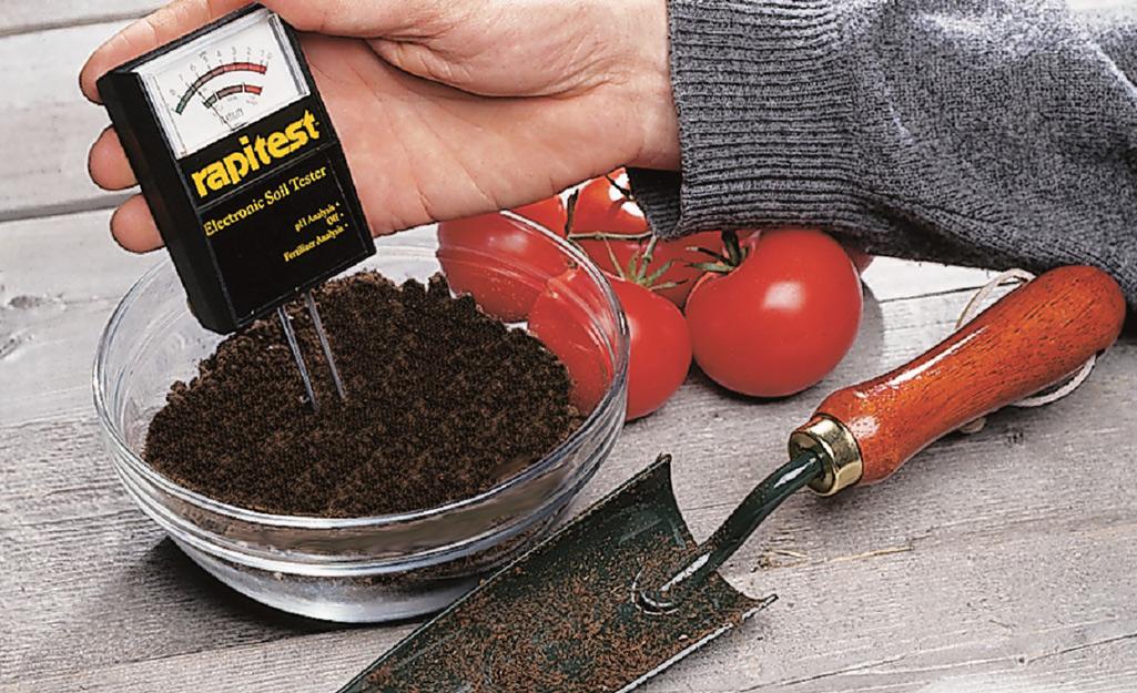 A gardener testing soil with a kit