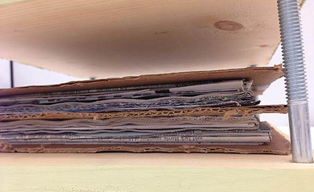 Các lớp bìa cứng và giấy trong một máy ép hoa.