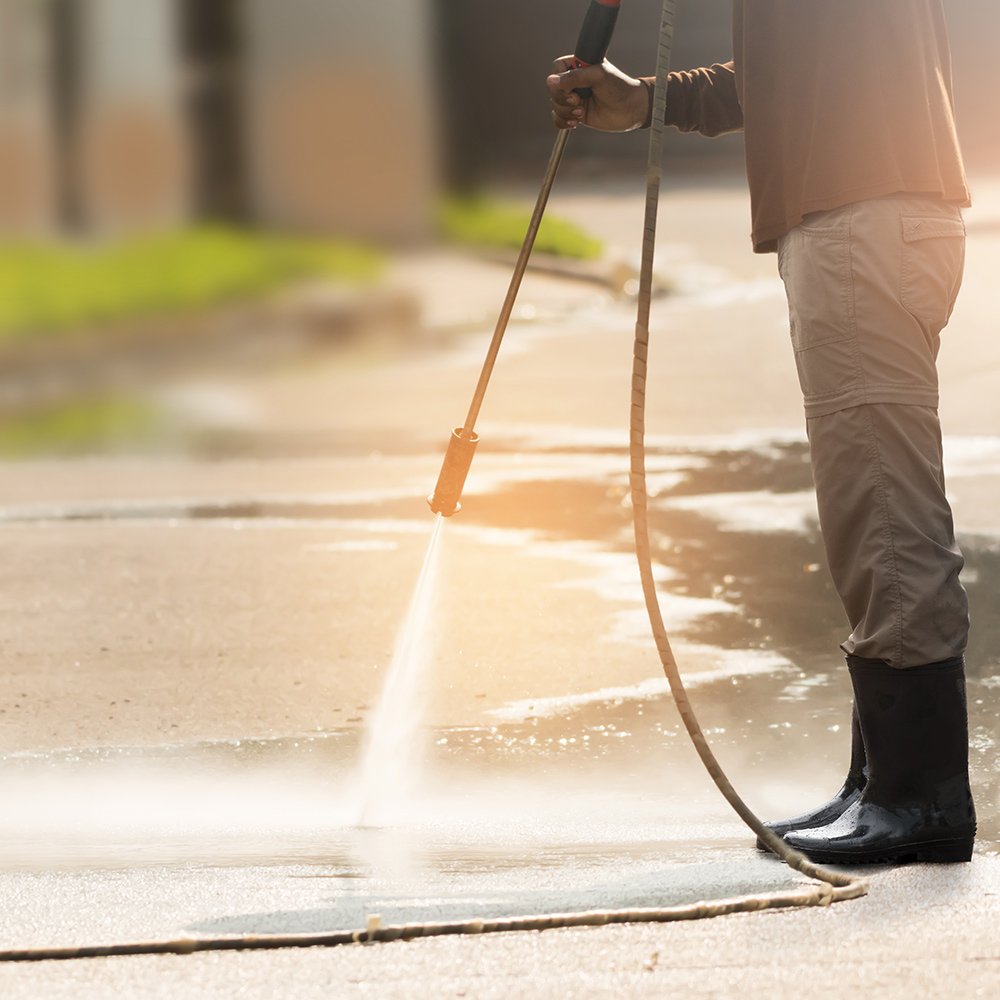 A person wearing khaki pants tucked into black rain boots sprays a concrete driveway with a pressure washer.