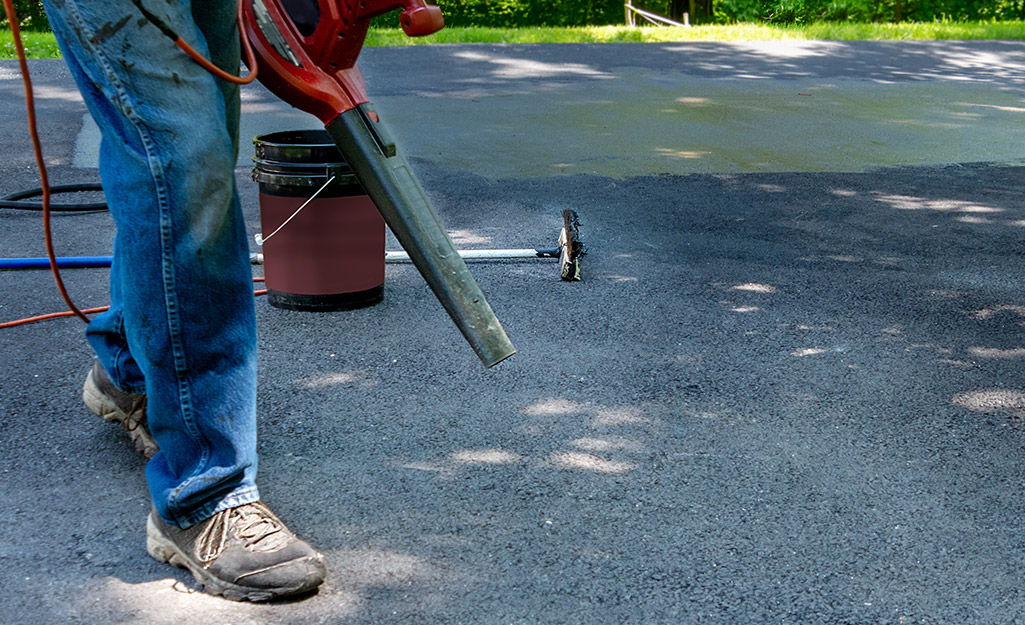 A person uses a leaf blower to remove dirt and debris from a concrete driveway.