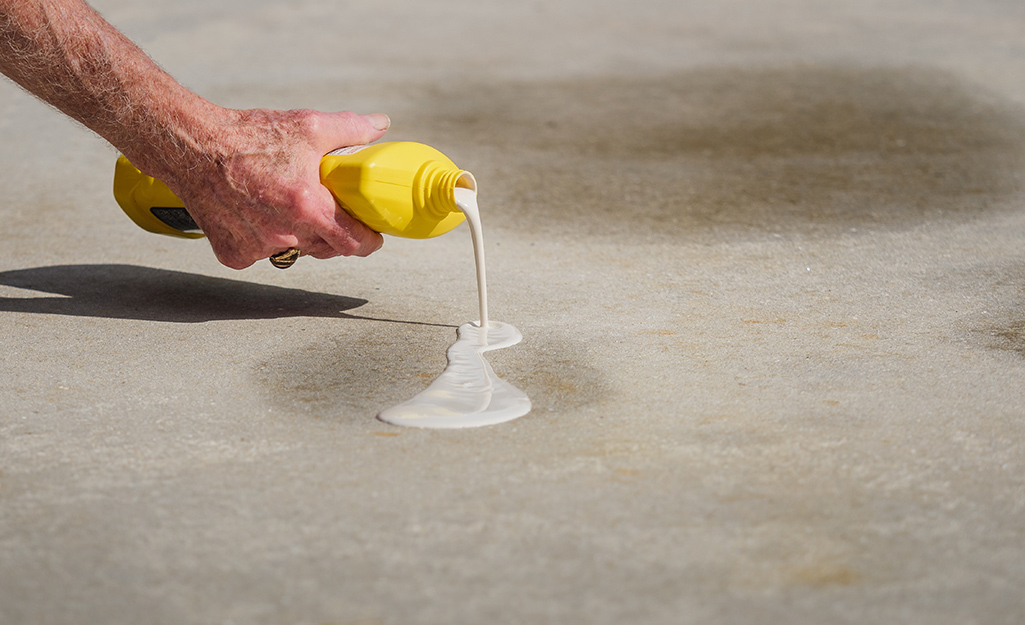 A person pours degreaser from a yellow bottle onto a concrete driveway stain.