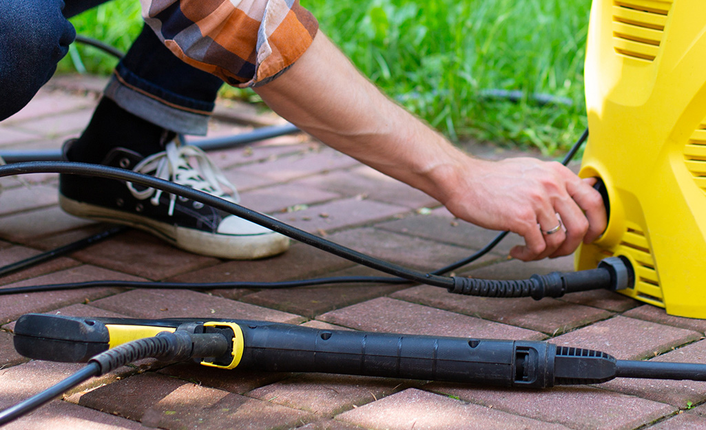 A person wearing black sneakers and rolled up jeans squats down to attach a hose to a yellow pressure washer.