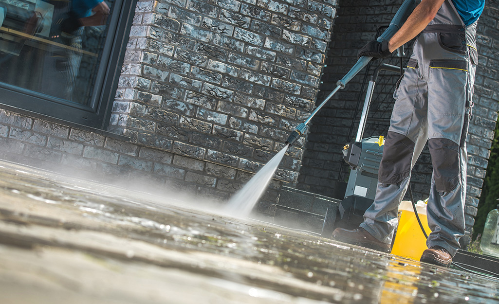 A person uses the spray wand of a pressure washer to spray water on a concrete driveway next to a brick building.