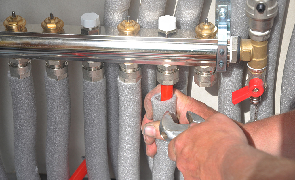 A person foam wrapping pipe insulation around exposed water pipes.