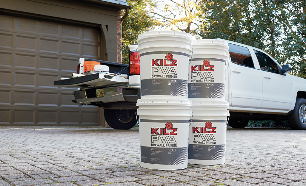 Four buckets of primer placed on a driveway next to a pickup truck.
