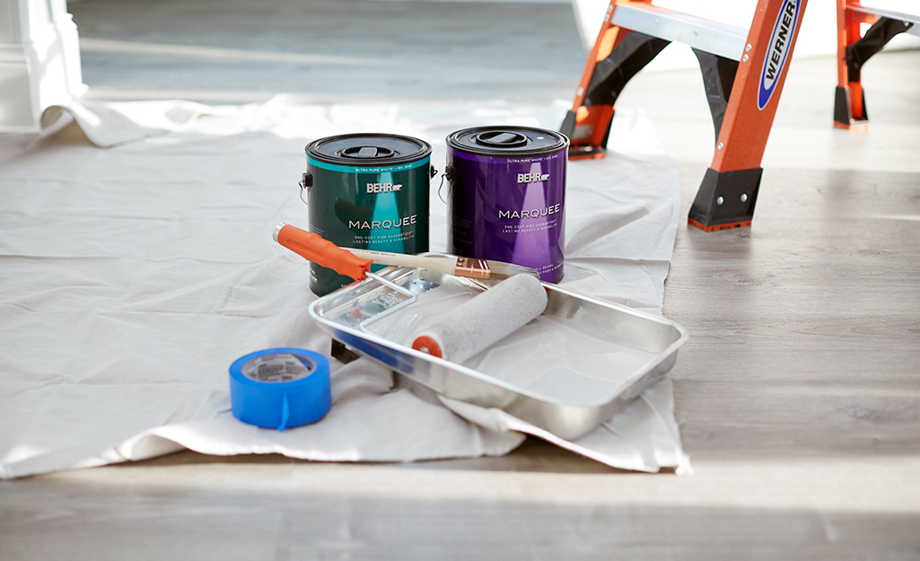 Paint primer, painter's tape, a paint roller and paint tray placed on a drop cloth on a floor.