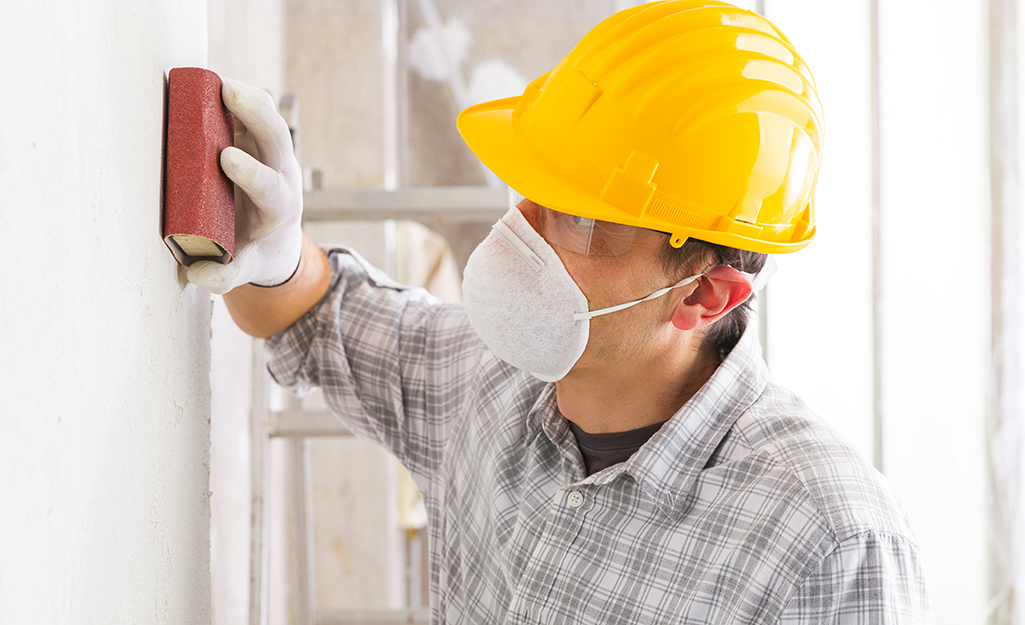 a person wearing a dust mask using a sanding block to smooth a coat of primer on a wall.