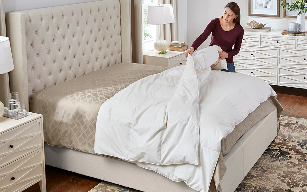 Woman is pulling her duvet in preparation for the cover.
