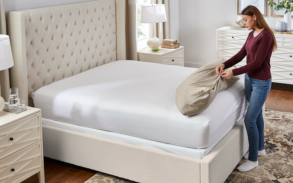 Woman is fastening together the duvet cover and comforter.
