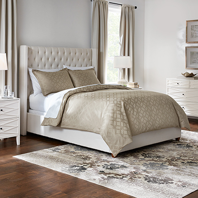 A made bed with neutral-colored bedding.