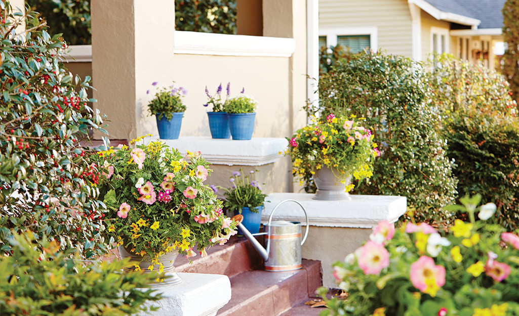 Many flowering plants in planter containers and a watering can are placed on a home's front porch.
