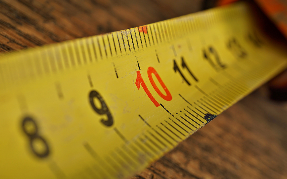 Tape measure head anchored to a point for stability.