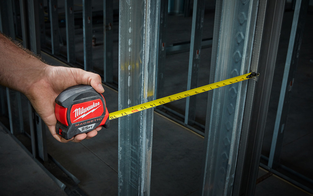 A woman measuring a project with a tape measure.