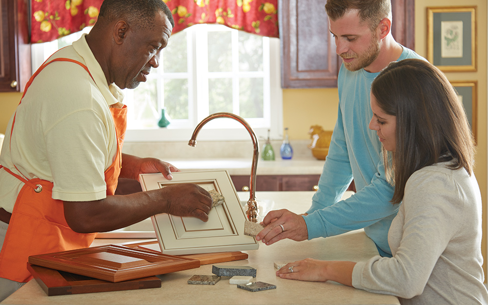 A refacing professional discussing a cabinet refacing finish with a man and a woman in a kitchen.