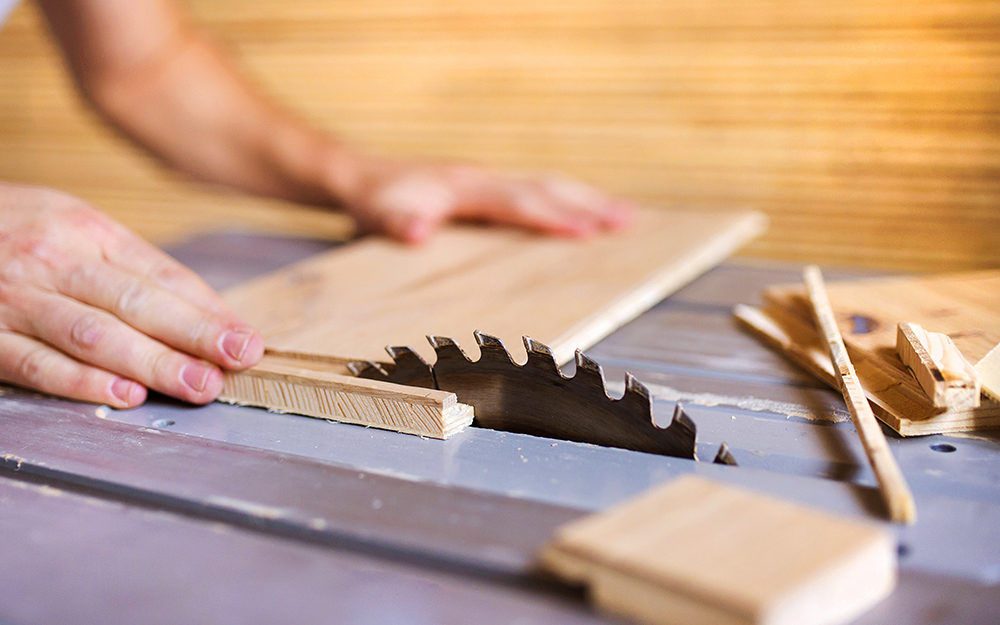 A person cutting plywood for a cabinet refacing.