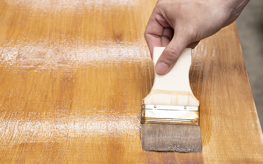 A person applying polyurethane to a cabinet surface after refacing.