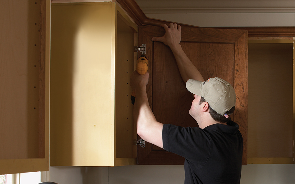 A  person reattaching a door to a kitchen cabinet.