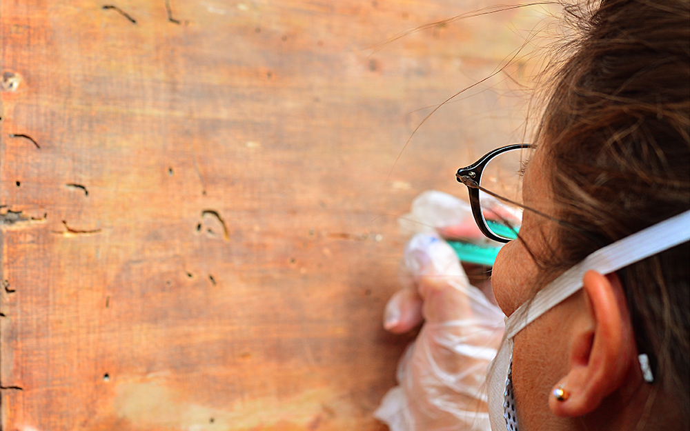 A person adding filler to a piece of wood.