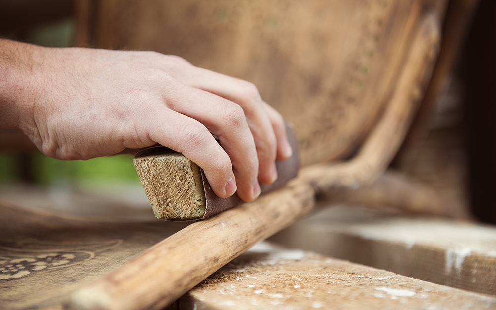 A person sanding the finish off a wooden chair.