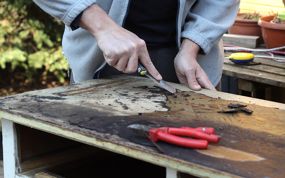A person stripping the finish off a wooden dresser top.