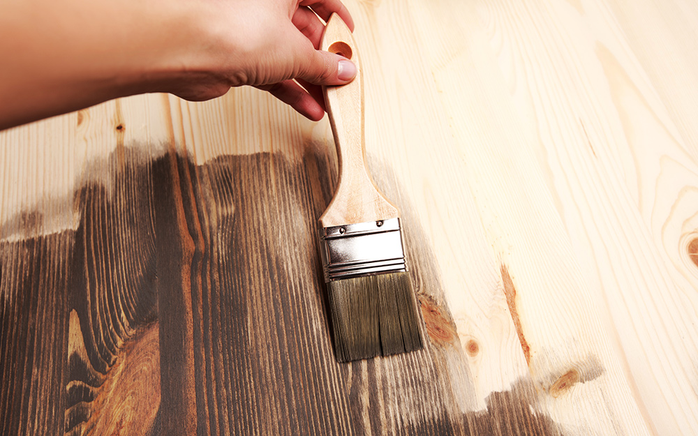 A person applying stain to a piece of wood.