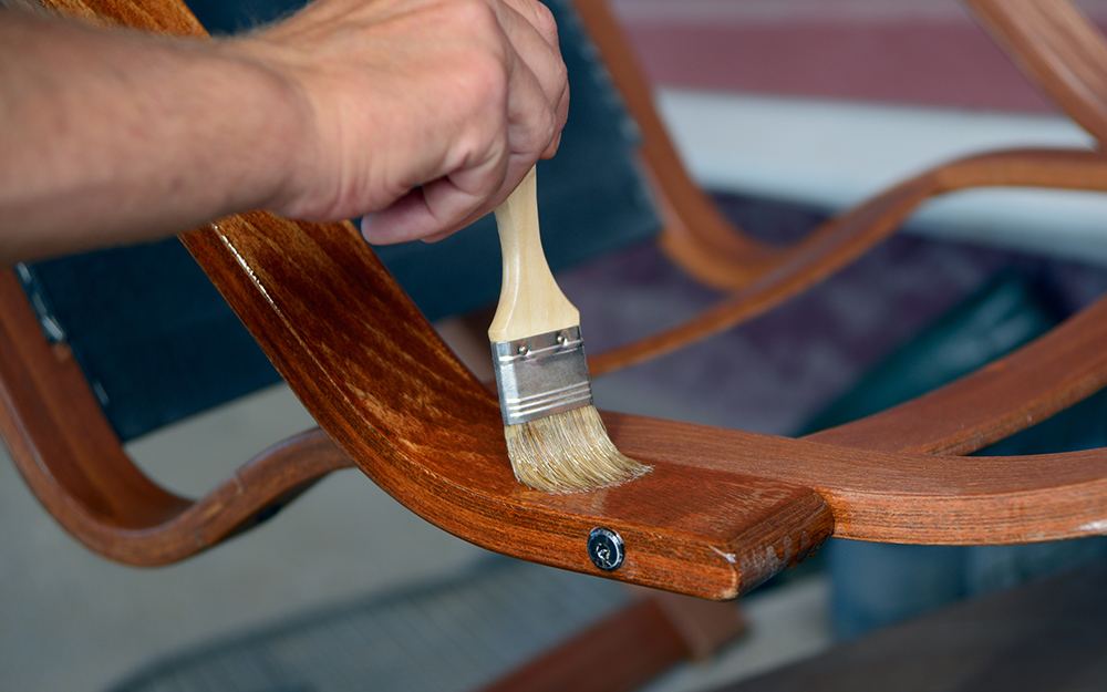 A person applying finish on to a wood furniture piece.