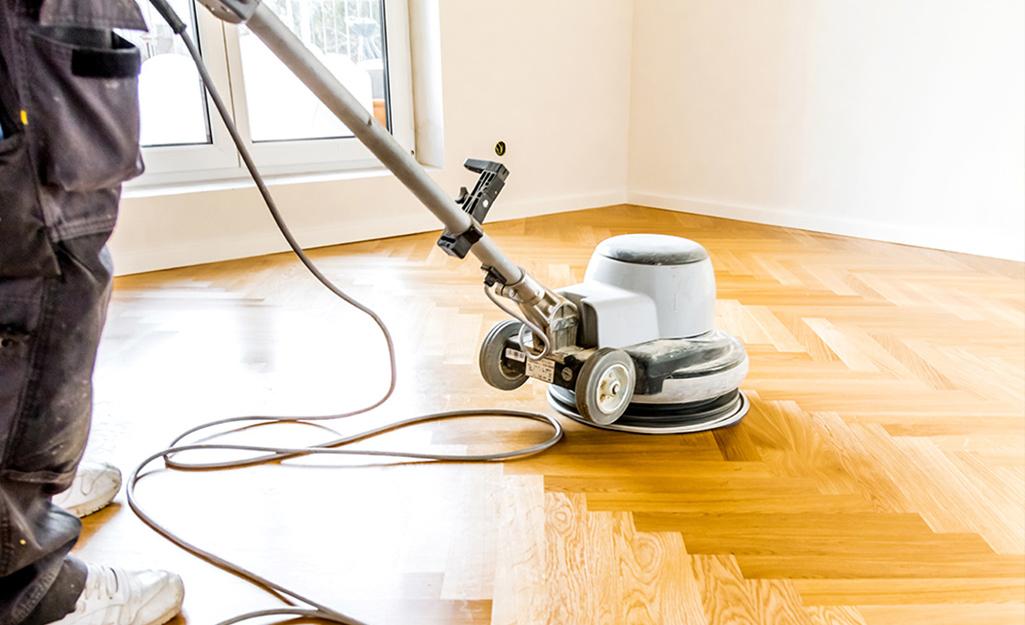 A person uses a floor buffer on a hardwood floor.
