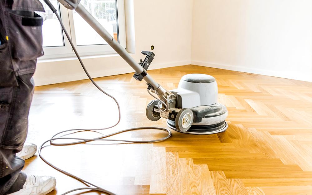 person using a floor buffer on hardwood floor