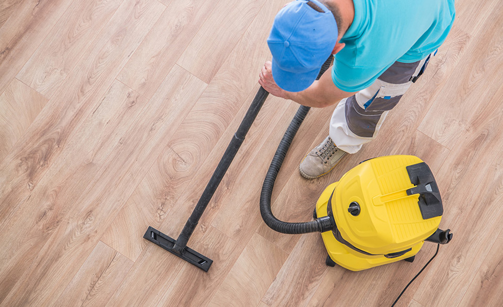 A person vacuums the dust from a hardwood floor.