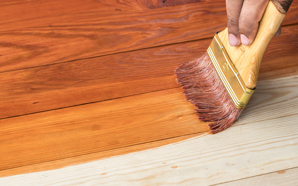 person using a paintbrush to apply stain to hardwood floor