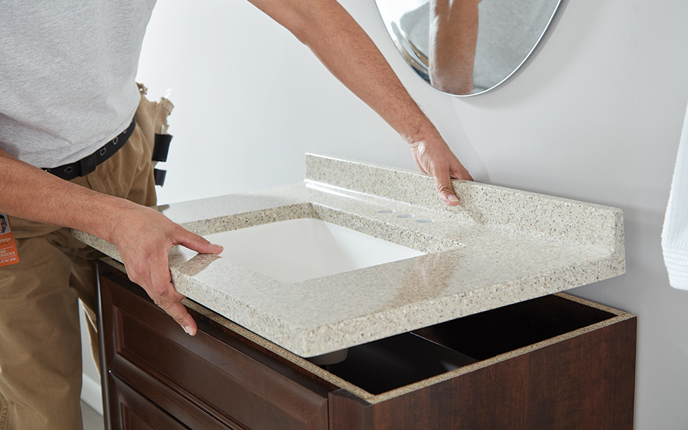 A new sink is installed on top of a bathroom vanity while remodeling a bathroom.